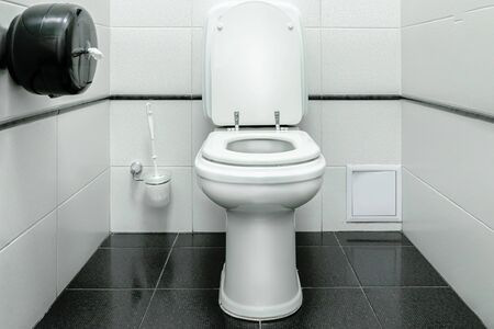 Toilet, toilet room in the style of minimalism. White walls and black floor. Graphics and contrast. Standard-Bild