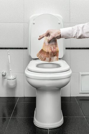 Currency and financial crisis in Russia - a person throws Russian currency in the toilet. the fall of the Kusa to the us dollar financial storm and instability. Hand and rubles close up 写真素材