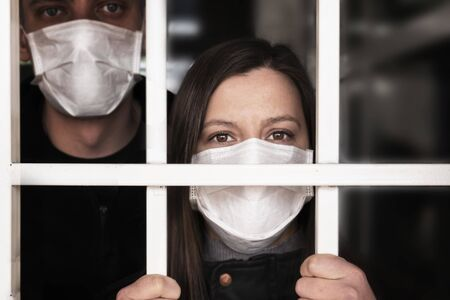 A woman in a mask , looking intently at the camera. Quarantine and isolation of patients with covid coronavirus 2019. Isolation grid, incarceration and illness. pandemics and epidemics,