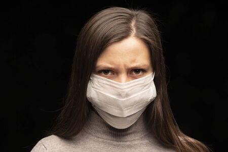 a womans tense and restless gaze at the camera. Portrait of a puppy in a white medical mask close-up. The danger of the spread of viruses and protection. Fear of the future