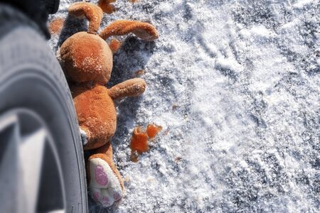 childrens accident on a winter road, Bunny rabbit toy. Death on the road, carelessness and danger. Attention and caution. roadkill winter, blood on snow. Concept copy space