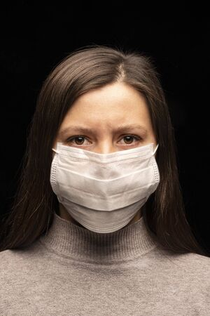 a woman in a mask , a tense, restless look at the camera. concern about a coronavirus infection , an attempt at protection. Studio portrait close -up. vertical photo