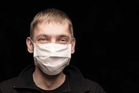 a man in a medical protective mask from infections, something is happy and laughing, at a time when the world is raging epidemics and a coronavirus pandemic. Foolish man