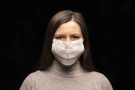 a woman in a mask , a tense, restless look at the camera. concern about a coronavirus infection , an attempt at protection. Studio portrait close -up