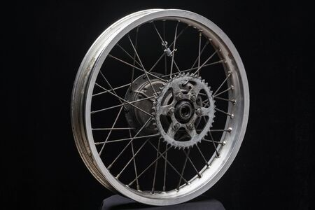 the rear wheel of a motorcycle without a tire, with a motorcycle sprocket, old used. close-up black background.