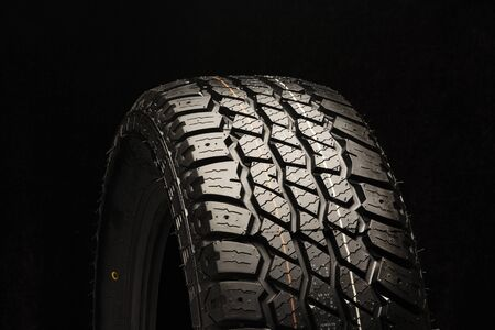 all terrain new tire close-up on a black background