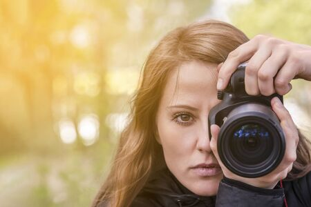 photographer girl, close-up portrait. The girl model takes photos, looking at the viewer and into the lens of the outdoor camera. red hair develop, copyspace