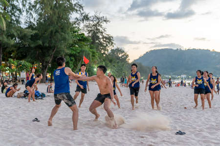 Thailand, Phuket, March 30, 2020: men and teenage girls from China play soccer and Rugby with a ball on the beach. sharp fighting and duels, cheerful mood and laughter