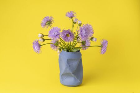 bright summer bouquet of purple field daisies in an old blue jar on a yellow background