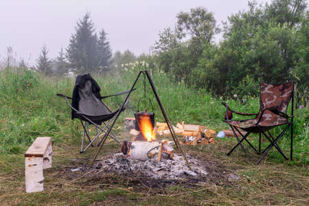 bonfire in nature. the kettle is warming in the flame. Cozy outdoor camping in a clearing in the forest 写真素材