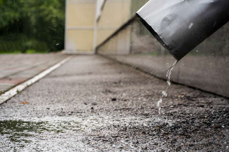 drain water through a pipe, raindrops, puddle and bad weather on the street. Illustration for the weather forecast.