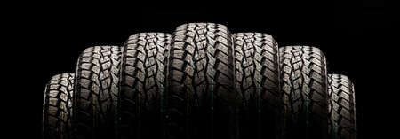 tires on a black background in a row, panoramic photo.