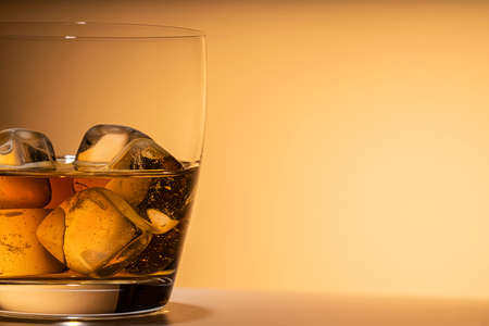 glass of whiskey on the rocks close-up. or other alcohol: Bourbon, cognac, or liqueur. Orange background, free space for text, copy space. 版權商用圖片