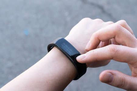 communication technologies concept-close up a woman sets up a smart watch before training. Foto de archivo