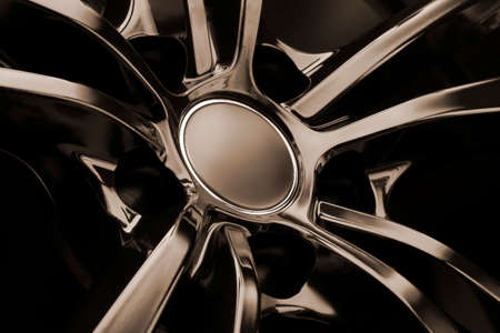 Black Gloss alloy wheel on a dark background. Stylish and expensive. mocap hub cap, reflection.