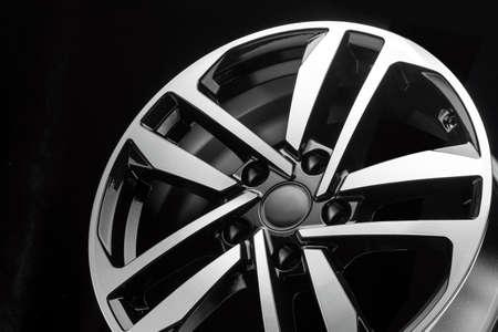 new shiny alloy wheel on black background, close-up details