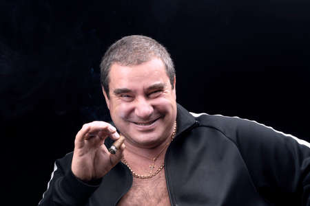 a kind, genuinely laughing white fat man, smoking a cigar. sincere emotions. A good-natured adult man, a portrait on a black background