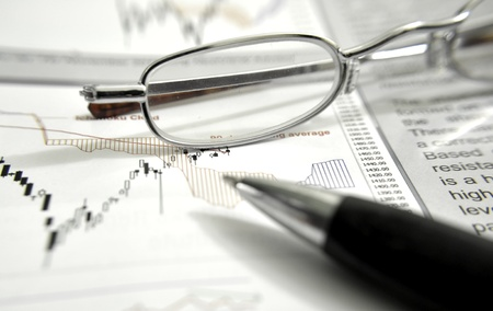 Eye glasses and pen on financial statistic