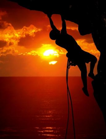 登る: ロック クライミングの日没時に 写真素材