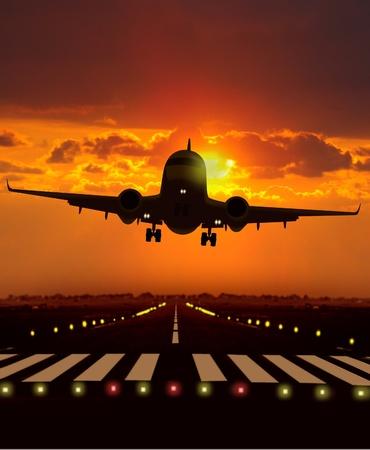 日没時に飛行機が離陸します。 写真素材