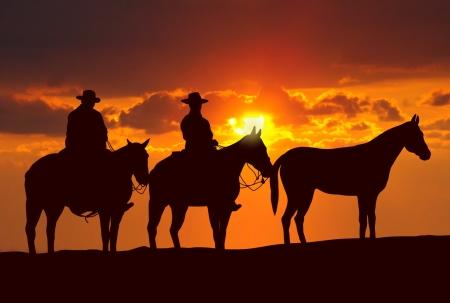 カウボーイと日没の下に馬