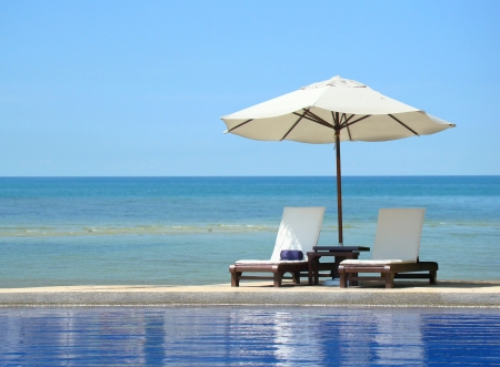 idling:  Two chairs and white umbrella on the beach