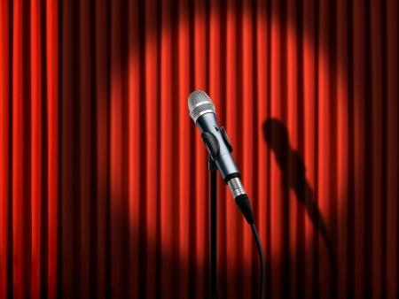 cortinas rojas: Micr?fono bajo proyector sobre cortinas rojas Foto de archivo