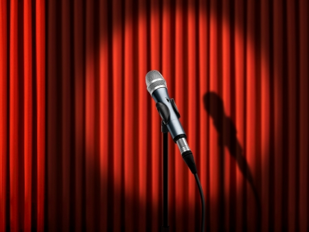 Microphone under spotlight over red curtains photo
