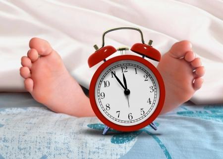 目覚まし時計で自宅の毛布の下で眠っています。 写真素材 - 20899210