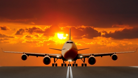 日没時の滑走路に飛行機離陸