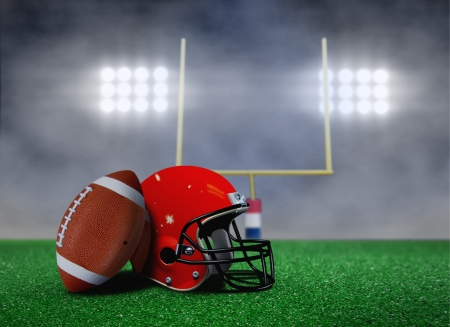 American Football and Helmet on Field with Goal Post under Spotlights Stock Photo