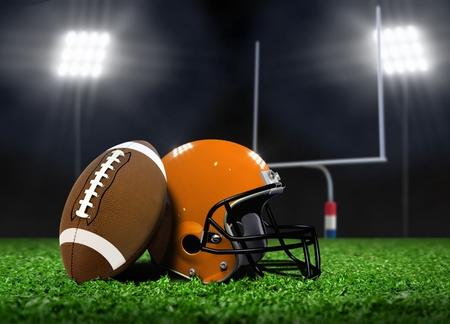 Boule du football et casque sur l'herbe sous projecteurs