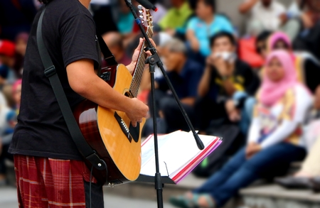 acoustical: street musician with guitar, with audience in background