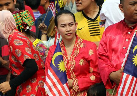 merdeka: Kuala Lumpur, Malaysia - August 31,2015 : Unidentified young  woman holding Malaysian flag during the Malaysian Independence day parade in Merdeka Square, Kuala Lumpur