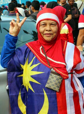 merdeka: Kuala Lumpur, Malaysia - Aug 31,2015 : Unidentified older woman wearing Malaysian flag costume with peace sign during the Malaysian Independence day in Merdeka Square, Kuala Lumpur