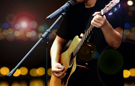 Chitarrista sul palco eseguendo con la chitarra acustica
