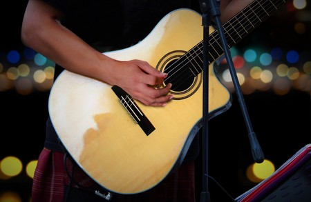 acoustical: Guitarist playing acoustic guitar with blur lights background