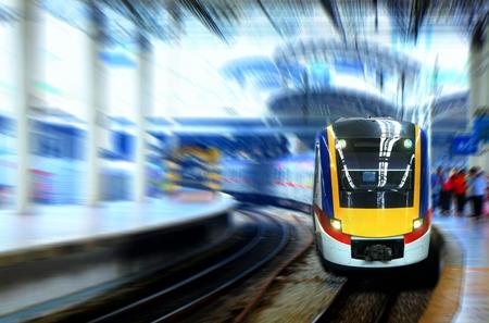 transport: Fast moving train leaving station platform Stock Photo