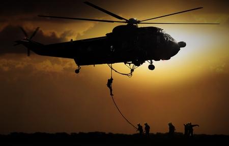 Helicóptero cayendo soldado durante la puesta del sol Foto de archivo