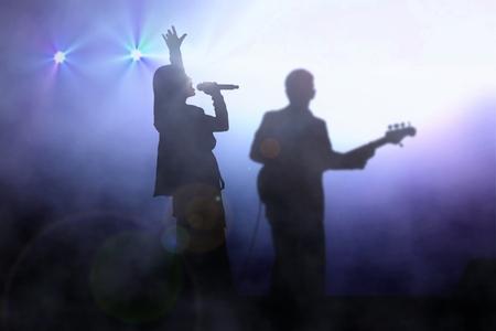 Women on stage singing with guitarist under spotlight Foto de archivo