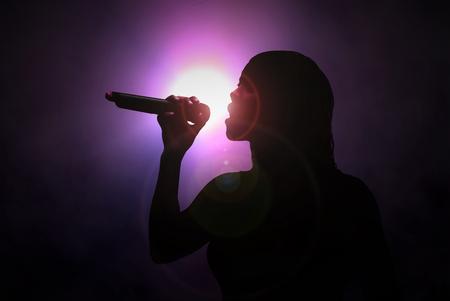 Mujeres cantando con el micrófono bajo proyector