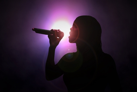 Women singing with microphone under spotlight Stock Photo - 57625007