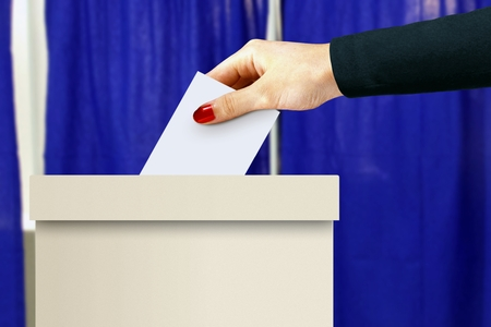 elect: Ballot box with women hand casting a vote Stock Photo
