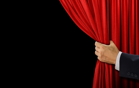 Hand open stage red curtain on black background Standard-Bild