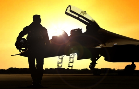 fighter jet: Military pilot on airfield walking away from the fighter jet