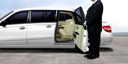 Driver waiting and standing next to the white limousine Imagens