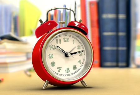 Red alarm clock on study desk