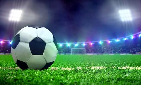 明るいスポット ライトとスタジアムのフィールドでサッカー ボール