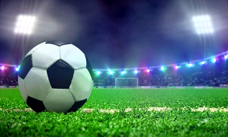 Soccer ball in a stadium field with bright spotlights