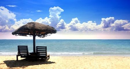 曇り青空と熱帯の砂のビーチチェア 写真素材